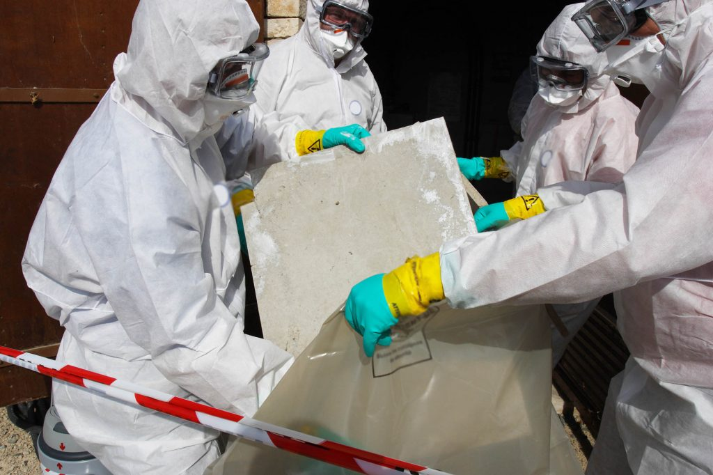 Protected with PPE construction employees safely removing asbestos