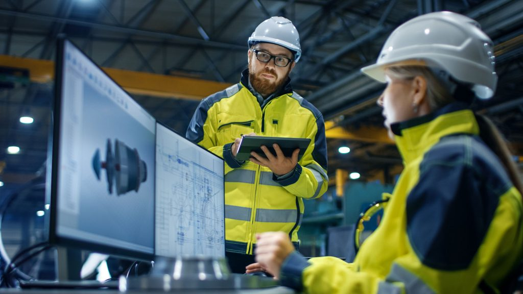 2 construction/manufacturing workers use 3d software to plan project at work