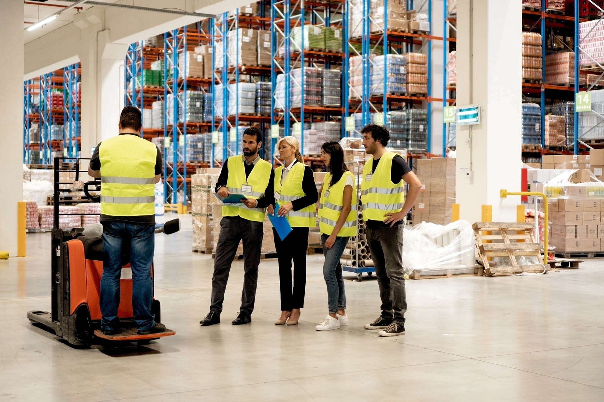 Warehouse staff learning to use forklift for proper storage management